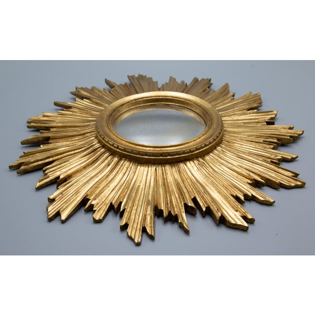 A stunning antique French gilded sunburst mirror, circa 1930. It retains the original slightly convex mirror which is...