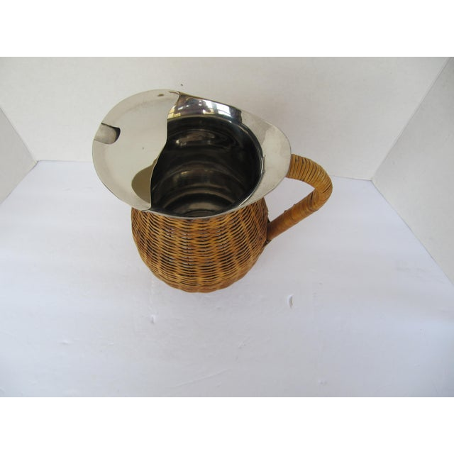 Vintage stainless pitcher wrapped in wicker. This unique piece is perfect for all of your summer entertaining.
