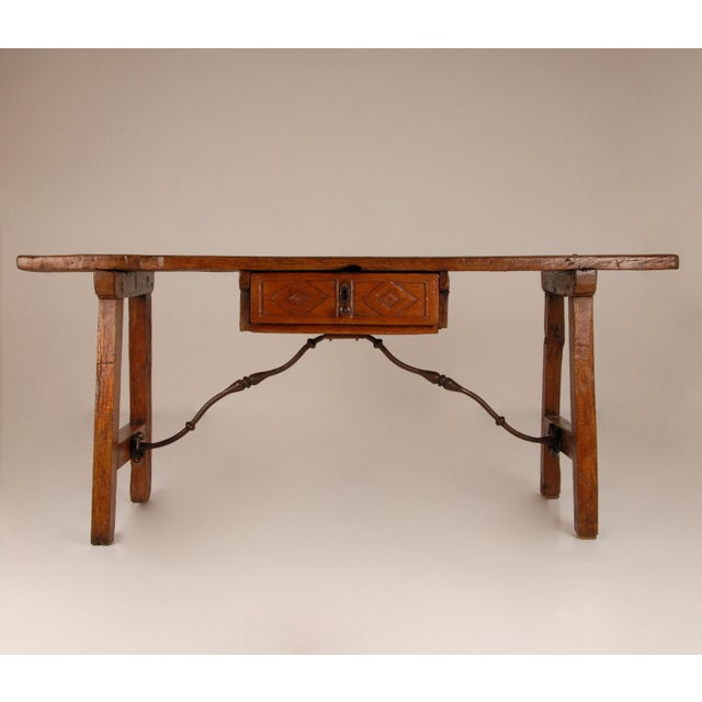 A late renaissance Spanish console table, side or sofa table. Made of walnut wood and wrought iron stretchers. The table...