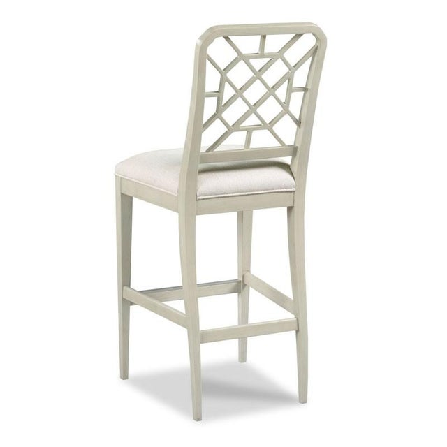 A pierced fretwork back rests above an upholstered seat that is raised by graceful tapering legs. Crafted from hardwood...