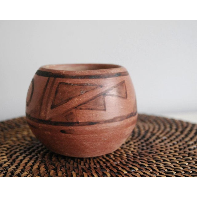 This small vintage Native American earthenware pot is a black on red pot -- hand coiled with a matte red slip glaze and...