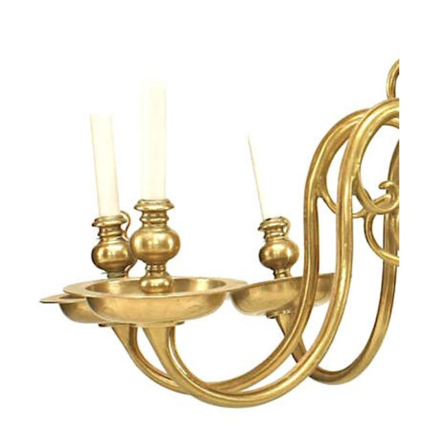 English Georgian style brass chandelier with eight scroll form arms and an open ring bottom (18th-19th century).