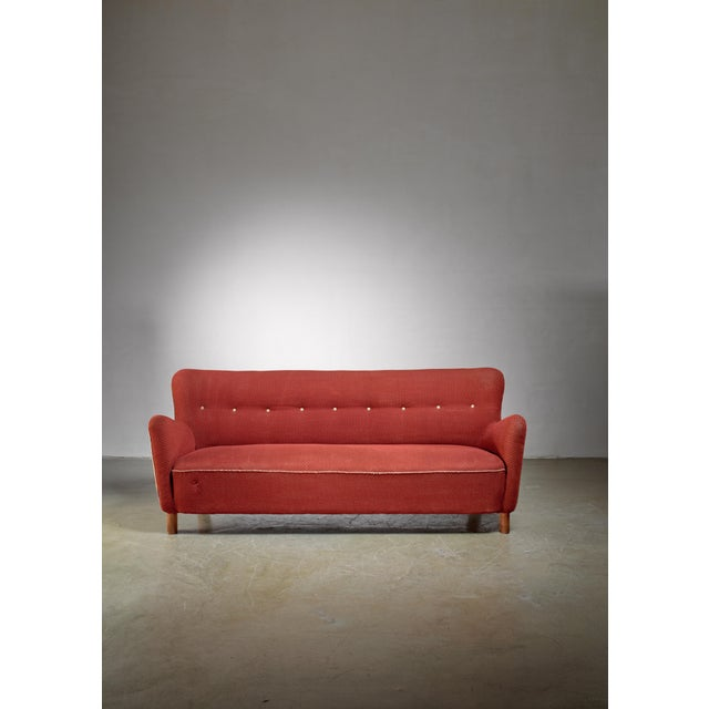 A Danish model 1669a sofa by Fritz Hansen. The sofa stands on stained beech legs and has a red patterned and buttoned...