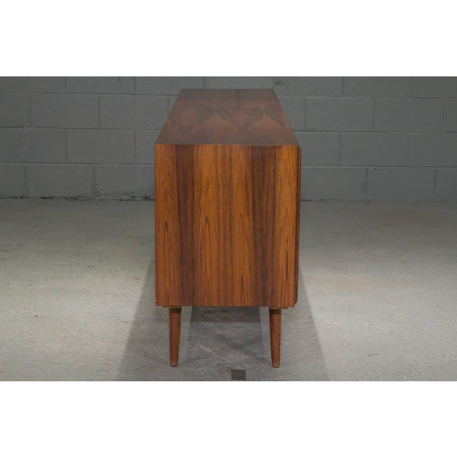 Danish Modern Rosewood SIdeboard. This sideboard features four sliding doors which open to reveal cutlery drawers on...