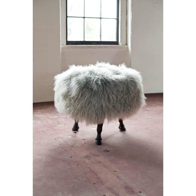 Tibetan wool covered ottoman sits on 4 carved mahogany horse hoof legs