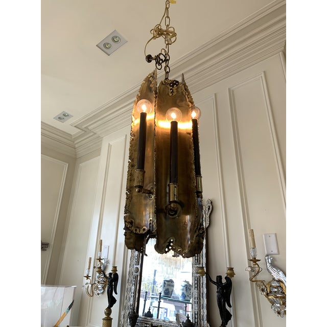 This is a torch cut brutalist chandelier by Tom Greene for Feldman. This light is in excellent condition with 7 bulbs...