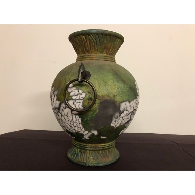 Tony Evans signed Raku vase with metal horse head handles. This 1980s vintage vase is mostly mottled green with swaths of...