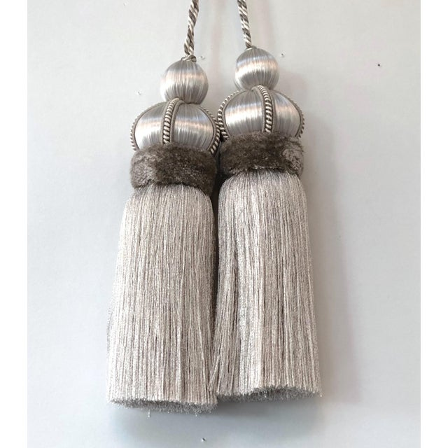 Pair of gray satin covered key tassels with cut velvet ruche above the skirt, decorative gimp and a twisted, three colored...