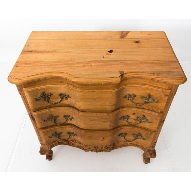 Carved French pine chest of drawers with carved scallop shell mirror, circa 20th century. The piece features a carved...