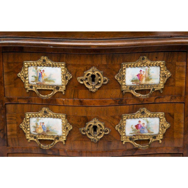 This is a beautifully detailed walnut specimen Louis XV bombe commode with three drawers exhibiting porcelain placques...