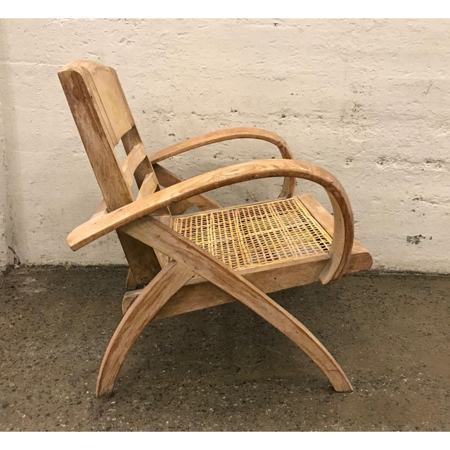 1950s cerused lounge chair attributed to Rene Gabriel. Has a collapsible back, a caned seat and rounded arms.