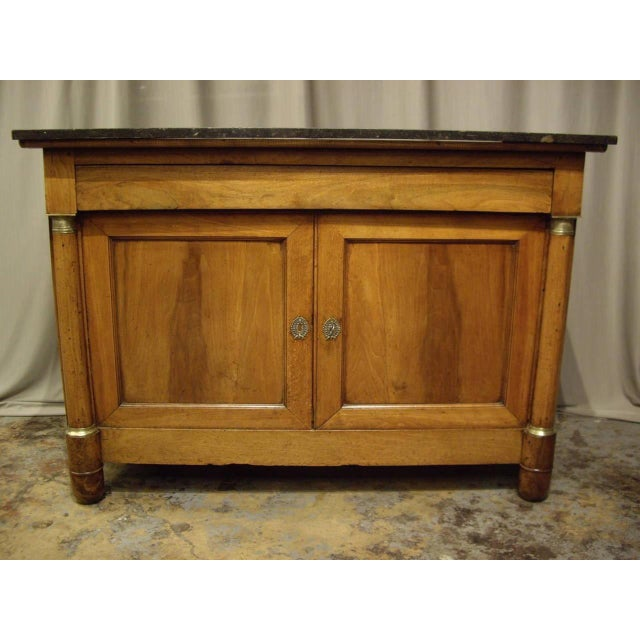 Honey colored patina French Empire walnut buffet with black marble top. Circa 1820.
