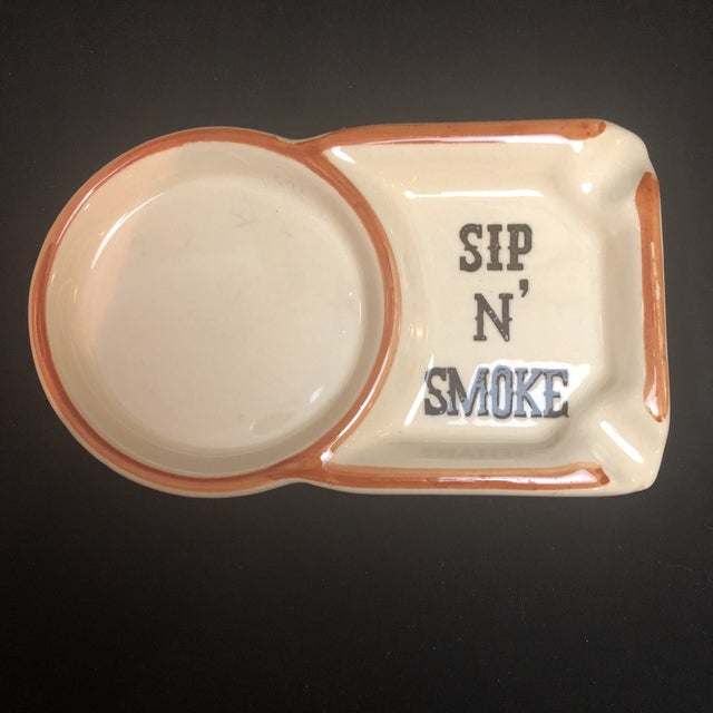 """A vintage ceramic coaster with attached ashtray with the words """"Sip N'Smoke""""."""