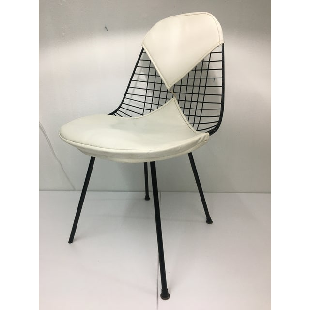 Authentic from the mid-century era, this classic Eames chair features a powder-coated black wire seat on the iconic black...
