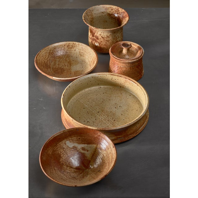 A set of five Franco Agnese ceramic pieces in earth tones; four bowls and a pot with lid. All pieces are signed underneath...