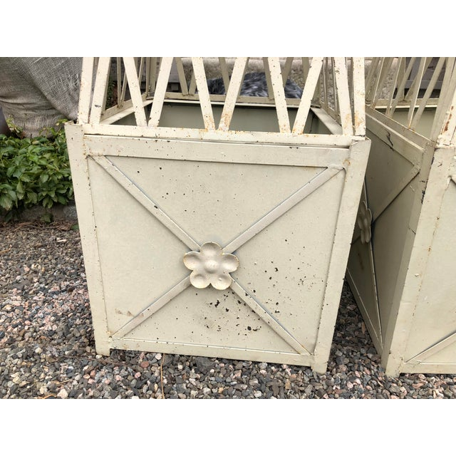 Handsome pair of vintage planters with accompanying obelisks. Planters are painted metal with florets on each side. The...
