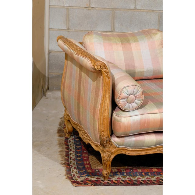 Mid-Century Louis XV style sofa or day bed featuring a pickled and carved wood frame and upholstered in beautiful, striped...