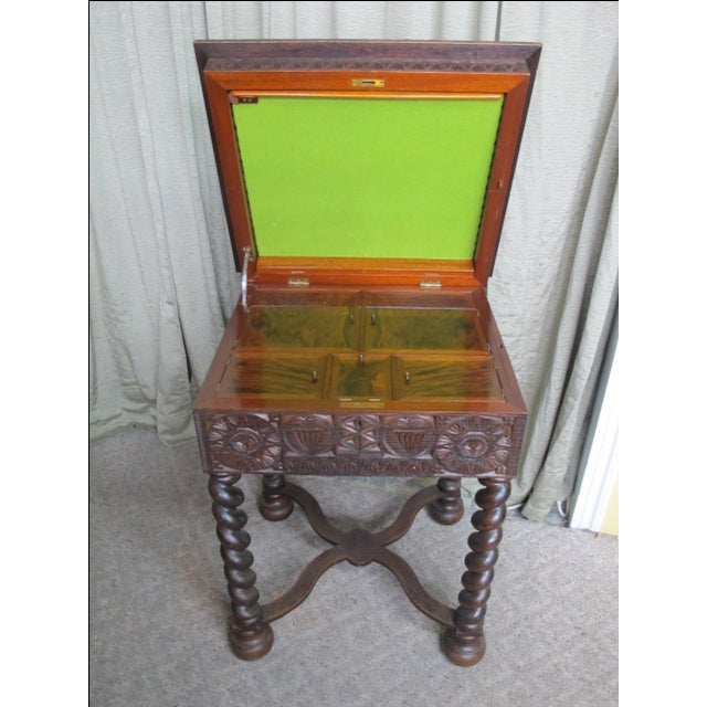 Elaborately carved late 19th century Swedish sewing table. In dark oak with carved top and apron featuring animal and...