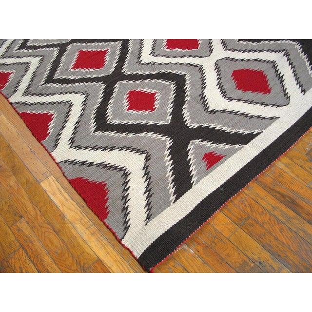 Beautifully woven in tones of black, white, red and gray, this Navajo rug is especially evident in the lovely variegation...