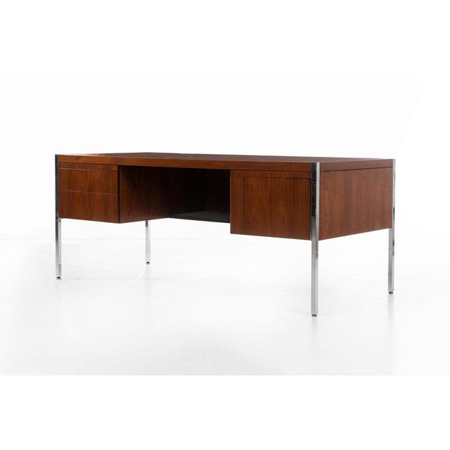 Richard Shultz (b. 1930) Executive desk in teak with chrome inlay, raised on chrome-clad steel legs. Features include two...