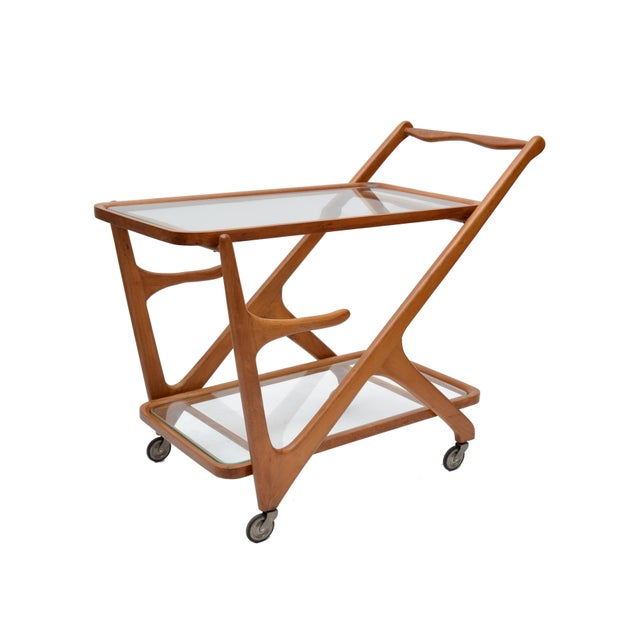Mid-Century Modern Italian bar cart by Cesare Lacca for Cassina. Featuring two glass shelves on a wooden frame. Height to...