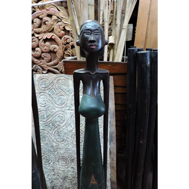 These long, lanky hardwood statues are contemporary takes on an Indonesian man and woman, with a possible Art Deco nod....