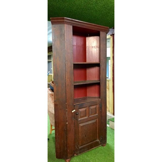 Wonderful very early corner cabinet with raised panel door. Dark patina  with painted barn red. Primitive Primitive Antique Pine ... - Primitive Antique Pine Corner Cabinet Chairish