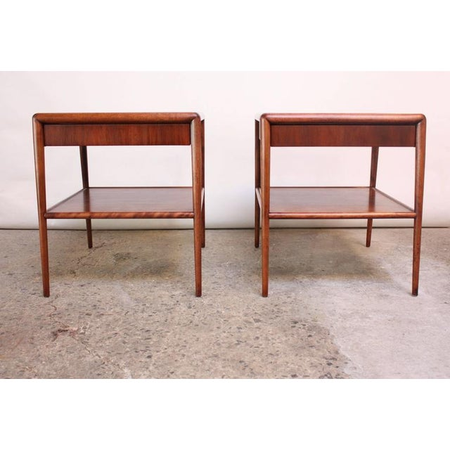 These scarce walnut end tables were designed by Robsjohn-Gibbings for Widdicomb in the 1950s and feature two tiers and a...