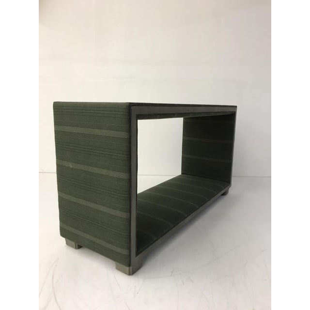 The Margaux Upholstered Console is a first quality market sample that features a Dark Green Fabric with a Slate Gray Finish.