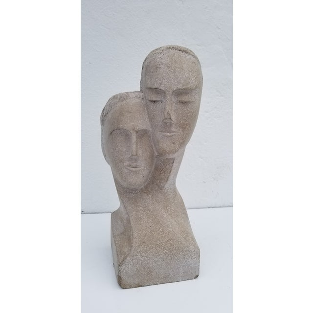 This is a stunning hand-carved stone sculpture depicting a man and woman. The piece was made circa 1960.