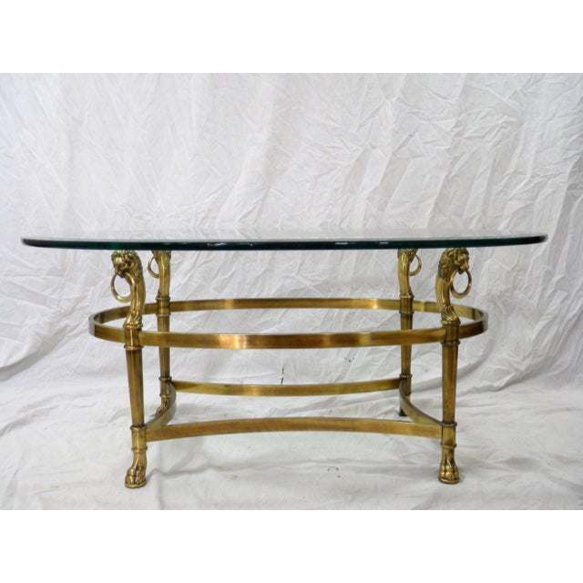 Vintage French Empire style brass and glass cocktail table. Made of solid brass with lion's head corner detail. Solid...