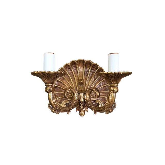 A pair of brass Neo-Rococo Spanish Sconces. A beautiful scalloped fan above acanthus scrolls forms the back for two curled...