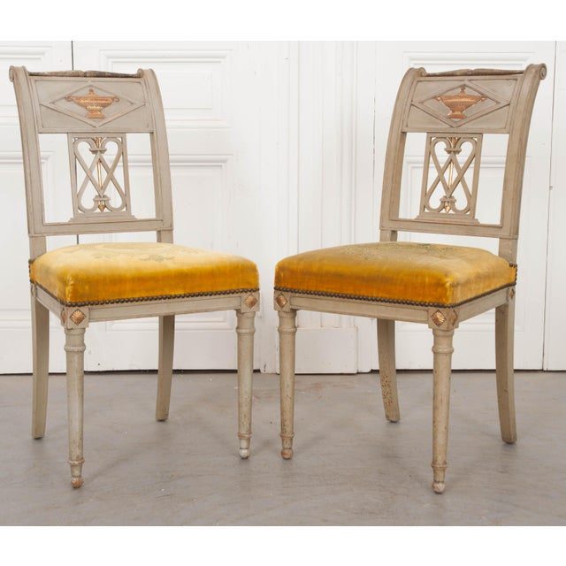 A fantastic pair of French Neoclassical-style painted and parcel-gilt side chairs by Albert Mallet, Paris, c. 1890....