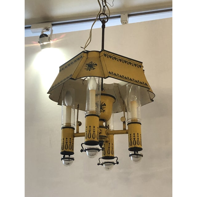 A wonderful French vintage painted iron and tole light fixture having mustard background with black embellishments. There...