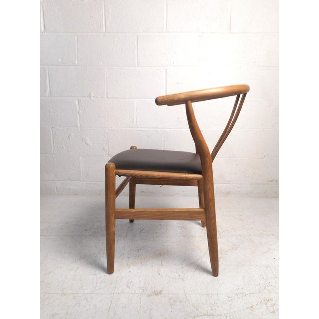"""This impressive mid-century style chair is modeled after Hans Wegner's famous """"Wishbone"""" design. Featuring a sturdy oak..."""
