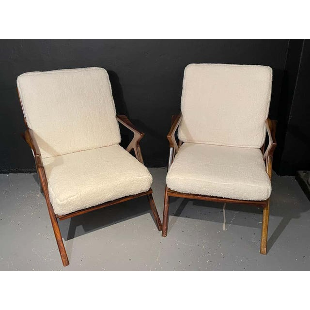 Pair of wooden slat back and seat Mid-Century Modern rosewood or walnut armchairs having been newly upholstered in a plush...