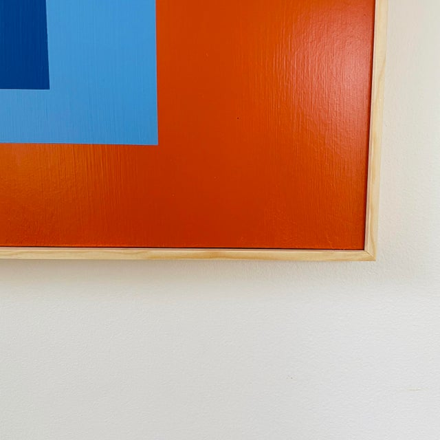 """Painting in the style of Josef Albers' """"Homage to the Square"""" with natural wood frame."""