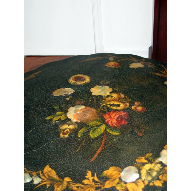 This listing is for a paper mache tilt top table with mother of pearl inlays and decorated with hand painted gold trims...