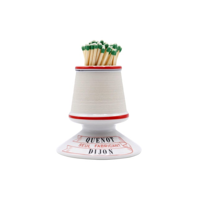A Parisian café ceramic match striker and holder. Decorated with a red line around the top and middle, with red and black...