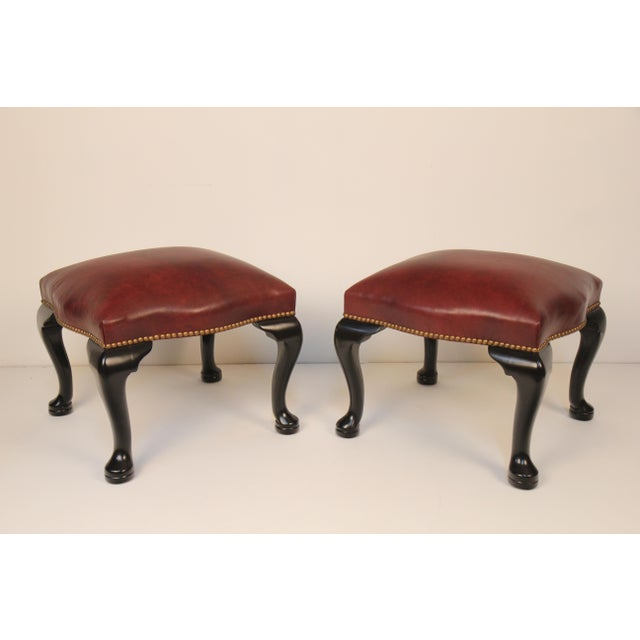beautiful pair of black lacquer English benches with burgundy leather upholstery and antiqued brass nail heads. Made by...