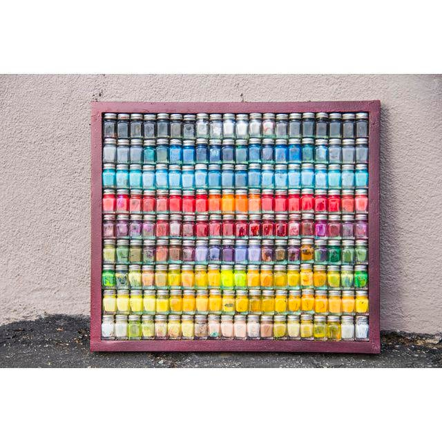 """A tapestry of vivid colors depicted by a mosaic of re-purposed enamel paint bottles, the """"Spectrum"""" framed wall art piece..."""