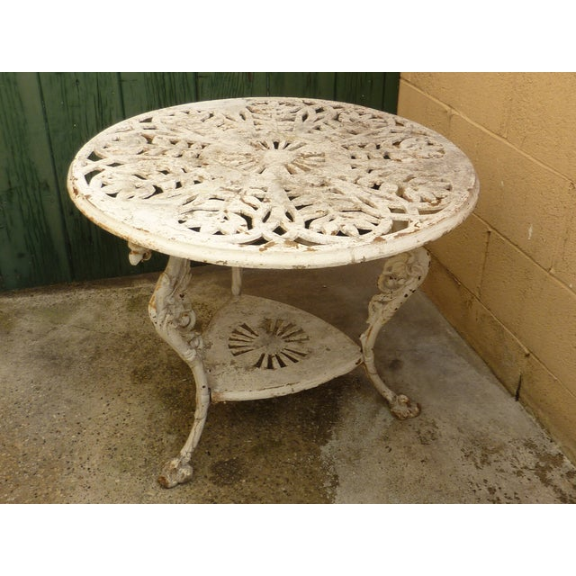 Beautiful antique cast iron garden table with pierced leaf design on the tabletop surface and griffen legs. Old, original,...