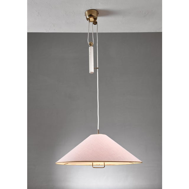 A Paavo Tynell model 1998 chandelier with a beige linen covered shade and white fabric diffuser with brass grip...