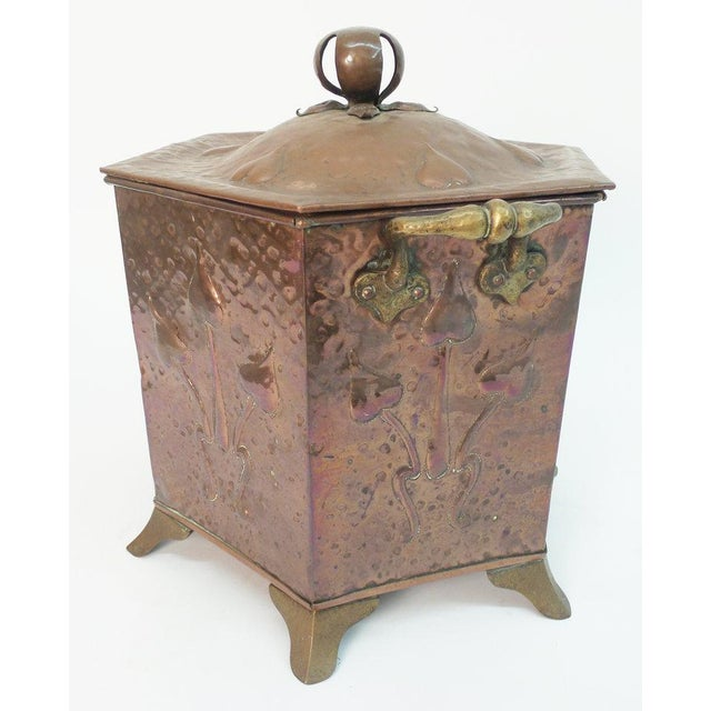 An Art Nouveau period hammered copper coal scuttle of hexagonal form and having brass feet and handles, England, circa 1885.