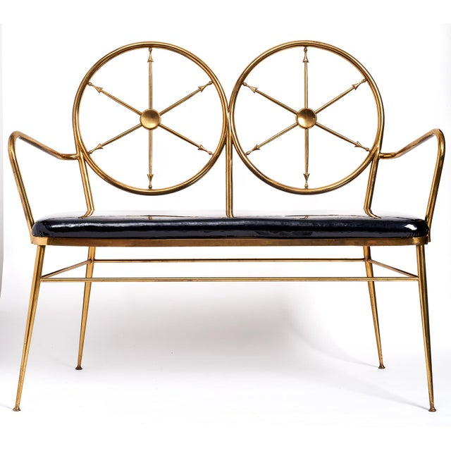 A whimsical entry bench with brass 'ships wheels' and patent leather upholstery. After Gio Ponto. Italian, circa 1950....