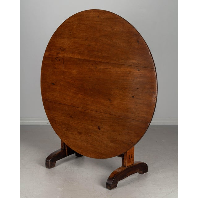 A 19th century French wine tasting, or tilt-top table, made of solid walnut. The top is made from three planks of walnut...