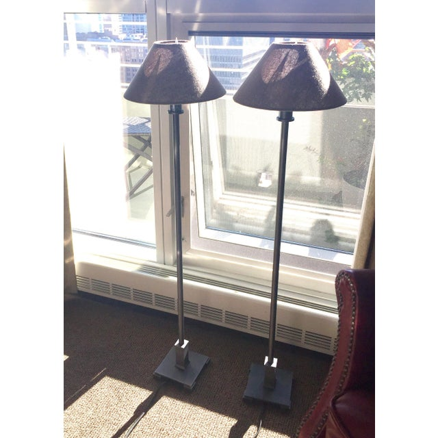 Less than one year old; pristine condition; simple, elegant but unobtrusive pair of lamps. Bronze base; black linen shade....