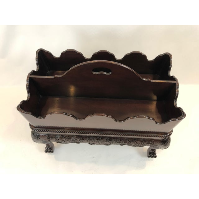 An unusually impressive ornate magazine rack made of rich dark mahogany, having a scalloped removable tip tray with two...