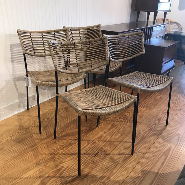 """Side chairs in natural unfinished pole rattan with black iron hairpin legs. Dimensions: W21.25 x D22.4 x H30.65"""" Brand..."""