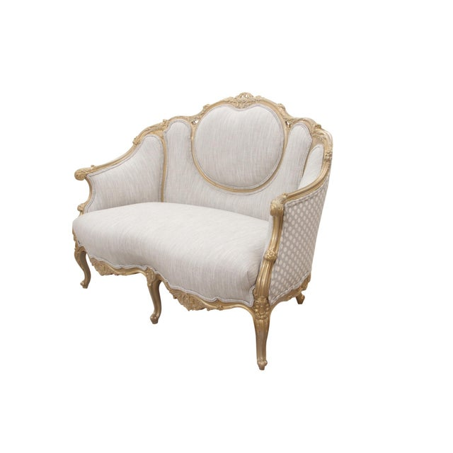 A Louis XV style settee with a central cameo back. Carved throughout with acanthus leaves and flowers, the settee is...